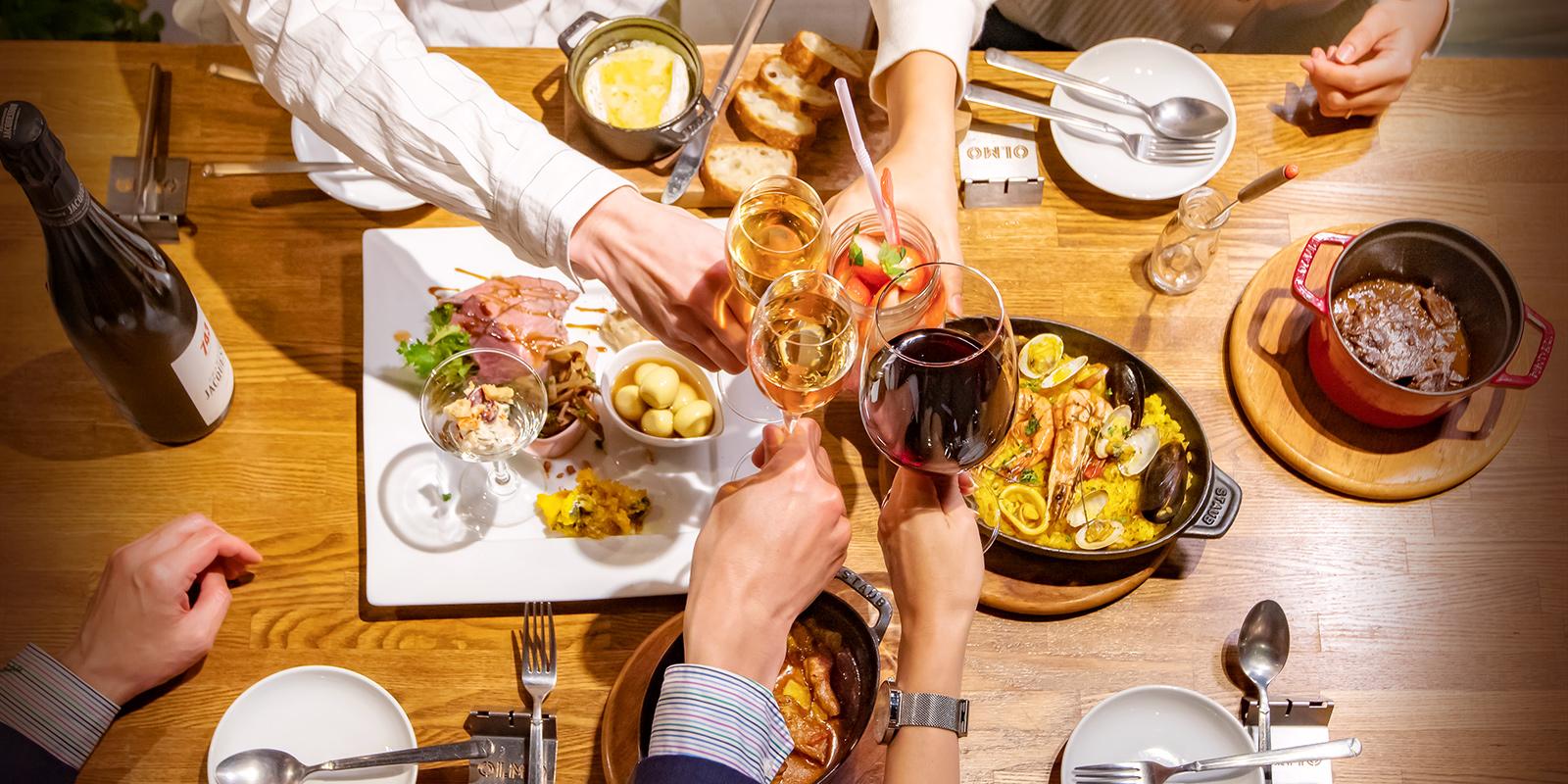 料理の並んだテーブルで乾杯する光景